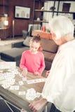 Σκοτεινός-μαλλιαρό προσχολικό κορίτσι που μελετά τις επιστολές με τη γιαγιά στοκ εικόνα