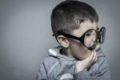 Σκοτεινός-μαλλιαρός νέος σπουδαστής με τα μεγάλα γυαλιά που σκέφτεται τη χειρονομία Στοκ εικόνα με δικαίωμα ελεύθερης χρήσης