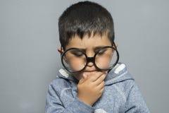 Σκοτεινός-μαλλιαρός νέος σπουδαστής με τα μεγάλα γυαλιά που σκέφτεται τη χειρονομία Στοκ εικόνες με δικαίωμα ελεύθερης χρήσης