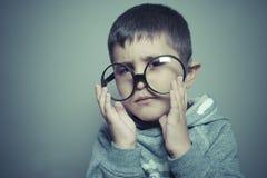 Σκοτεινός-μαλλιαρός νέος σπουδαστής με τα μεγάλα γυαλιά που σκέφτεται τη χειρονομία Στοκ φωτογραφία με δικαίωμα ελεύθερης χρήσης