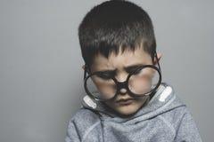 Σκοτεινός-μαλλιαρός νέος σπουδαστής με τα μεγάλα γυαλιά που σκέφτεται τη χειρονομία Στοκ Φωτογραφία
