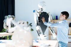Σκοτεινός-μαλλιαρό αγόρι σχετικά με το μπροστινό μέρος ενός ανθρώπινου ρομπότ Στοκ φωτογραφία με δικαίωμα ελεύθερης χρήσης