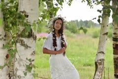 Σκοτεινός-μαλλιαρό κορίτσι με τις πλεξούδες και τις μαργαρίτες Στοκ φωτογραφία με δικαίωμα ελεύθερης χρήσης