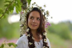 Σκοτεινός-μαλλιαρό κορίτσι με τις πλεξούδες και τις μαργαρίτες Στοκ Φωτογραφία