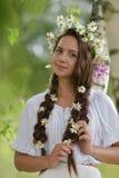 Σκοτεινός-μαλλιαρό κορίτσι με τις πλεξούδες και τις μαργαρίτες Στοκ εικόνες με δικαίωμα ελεύθερης χρήσης