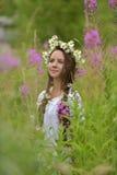 Σκοτεινός-μαλλιαρό κορίτσι με τις πλεξούδες και τις μαργαρίτες Στοκ Εικόνες