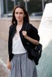 Σκοτεινός-μαλλιαρό κορίτσι που στέκεται στην οδό και που εξετάζει τη κάμερα στοκ φωτογραφία