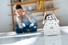 Σκοτεινός-μαλλιαρό μικρό παιδί που ελέγχει το άσπρο ρομπότ του Στοκ Εικόνα