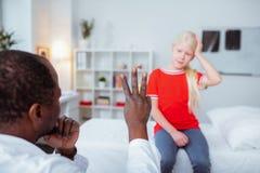 Σκοτεινός-ξεφλουδισμένος γιατρός που παρουσιάζει στο κορίτσι με τη διάσειση τρία δάχτυλα στοκ φωτογραφία με δικαίωμα ελεύθερης χρήσης