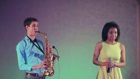 Σκοτεινός-ξεφλουδισμένος τραγουδιστής μαύρων γυναικών και λεπτός φορέας saxophone που αποδίδουν στη σκηνή απόθεμα βίντεο