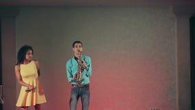 Σκοτεινός-ξεφλουδισμένος τραγουδιστής μαύρων γυναικών και λεπτός φορέας saxophone που αποδίδουν στη σκηνή φιλμ μικρού μήκους