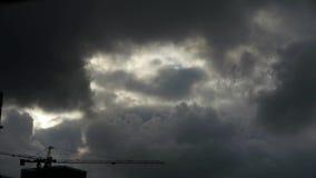 Σκοτεινός ουρανός κάλυψης σύννεφων, γερανοί, πολυόροφο κτίριο οικοδόμησης, σκιαγραφία σπιτιών απόθεμα βίντεο