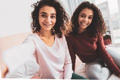 Σκοτεινός-eyed ακτινοβολώντας αδελφές που χαμογελούν ευρέως στοκ φωτογραφίες