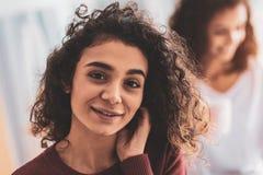 Σκοτεινός-eyed κορίτσι με τη σγουρή τρίχα που χαμογελά ευρέως στοκ εικόνα
