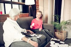 Σκοτεινός-eyed κορίτσι που φορά τα τζιν και το ρόδινο πουκάμισο που μελετούν με τη γιαγιά στοκ εικόνα