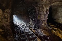Σκοτεινό βρώμικο εγκαταλειμμένο ορυχείο ουράνιου με τα σκουριασμένα υπόλοιπα του σιδηροδρόμου στοκ εικόνα με δικαίωμα ελεύθερης χρήσης