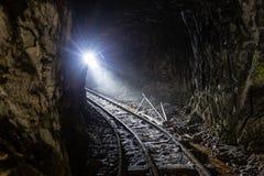 Σκοτεινό βρώμικο εγκαταλειμμένο ορυχείο ουράνιου με τα σκουριασμένα υπόλοιπα του σιδηροδρόμου στοκ εικόνες