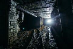 Σκοτεινό βρώμικο εγκαταλειμμένο ορυχείο ουράνιου με τα σκουριασμένα υπόλοιπα του σιδηροδρόμου στοκ φωτογραφίες με δικαίωμα ελεύθερης χρήσης