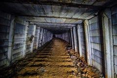 Σκοτεινό βρώμικο εγκαταλειμμένο ορυχείο ουράνιου με τα σκουριασμένα υπόλοιπα του σιδηροδρόμου στοκ εικόνα