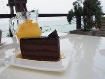 Σκοτεινό κέικ σοκολάτας στο πιάτο και το ποτήρι του χυμού από πορτοκάλι Στοκ Φωτογραφία