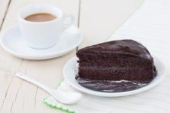 Σκοτεινό κέικ σοκολάτας στο άσπρο πιάτο στον ξύλινο πίνακα με τον καφέ Στοκ Φωτογραφίες