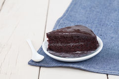 Σκοτεινό κέικ σοκολάτας στο άσπρο πιάτο στον ξύλινο πίνακα Στοκ φωτογραφίες με δικαίωμα ελεύθερης χρήσης
