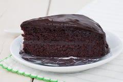 Σκοτεινό κέικ σοκολάτας στο άσπρο πιάτο στον ξύλινο πίνακα Στοκ εικόνα με δικαίωμα ελεύθερης χρήσης