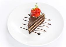 Σκοτεινό κέικ σοκολάτας στρώματος που διακοσμεί με την τεμαχισμένη κόκκινη φράουλα Στοκ Εικόνες