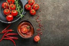 Σκοτεινό κεραμικό κύπελλο με τη σάλτσα ντοματών, φρέσκα λαχανικά, χορτάρια, πιπέρι σε ένα σκοτεινό υπόβαθρο Τοπ όψη Στοκ Εικόνες