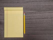 Σκοτεινό ξύλινο γραφείο, κίτρινο μαξιλάρι, μολύβι στο γραφείο Στοκ φωτογραφία με δικαίωμα ελεύθερης χρήσης