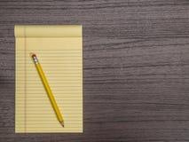 Σκοτεινό ξύλινο γραφείο, κίτρινο μαξιλάρι, μολύβι στο μαξιλάρι Στοκ Φωτογραφίες