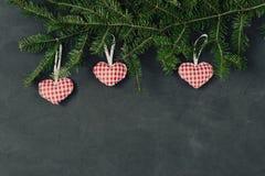 Σκοτεινό υπόβαθρο διακοπών Χριστουγέννων, φυσικές διακοσμήσεις που τίθενται σε μια σύνθεση με το χέρι - γίνοντα παιχνίδι κόκκινες Στοκ Εικόνες