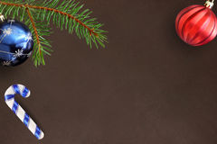 Σκοτεινό υπόβαθρο με τον κλάδο έλατου Χριστουγέννων, το ραβδί, την μπλε και κόκκινη σφαίρα Στοκ Εικόνα