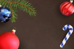 Σκοτεινό υπόβαθρο με τον κλάδο έλατου Χριστουγέννων, το ραβδί, την μπλε και κόκκινη θαμπή σφαίρα Στοκ φωτογραφία με δικαίωμα ελεύθερης χρήσης