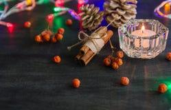 Σκοτεινό υπόβαθρο Χριστουγέννων με τα κεριά και τα μούρα της τέφρας βουνών Άσπροι κώνοι πεύκων Βελανίδια κλάδων Στοκ εικόνες με δικαίωμα ελεύθερης χρήσης
