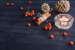 Σκοτεινό υπόβαθρο Χριστουγέννων με τα κεριά και τα μούρα της τέφρας βουνών Άσπροι κώνοι πεύκων Βελανίδια κλάδων Στοκ φωτογραφίες με δικαίωμα ελεύθερης χρήσης
