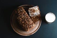 Σκοτεινό ψωμί δημητριακών με τους σπόρους ηλίανθων, ποτήρι του γάλακτος, σε έναν σκοτεινό πίνακα σχιστόλιθου υποβάθρου, έννοια τη Στοκ φωτογραφία με δικαίωμα ελεύθερης χρήσης