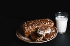 Σκοτεινό ψωμί δημητριακών με τους σπόρους ηλίανθων σε ένα πιάτο, ποτήρι του γάλακτος, σε έναν σκοτεινό πίνακα σχιστόλιθου υποβάθρ Στοκ εικόνα με δικαίωμα ελεύθερης χρήσης