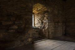 Σκοτεινό δωμάτιο με το παράθυρο τοίχων πετρών και την ξύλινη σκάλα Στοκ φωτογραφία με δικαίωμα ελεύθερης χρήσης