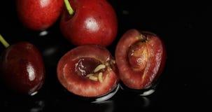Σκουλήκια φρούτων στο σάπιο κεράσι, μαύρο υπόβαθρο Προνύμφη των μυγών κερασιών closeup στοκ φωτογραφίες