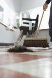 Σκουπίζοντας αποκόμματα τρίχας κομμωτών στο πάτωμα Στοκ Φωτογραφία