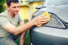Σκουπίζοντας αυτοκίνητο που χαμογελά το αρσενικό καθαρίζοντας αυτοκίνητο με το ύφασμα microfiber, αυτοκίνητο Στοκ φωτογραφία με δικαίωμα ελεύθερης χρήσης