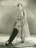 Σκουπίζοντας με ηλεκτρική σκούπα κουβέρτα γυναικών στοκ εικόνα με δικαίωμα ελεύθερης χρήσης