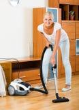 Σκουπίζοντας με ηλεκτρική σκούπα πάτωμα και έπιπλα νοικοκυρών Στοκ εικόνα με δικαίωμα ελεύθερης χρήσης