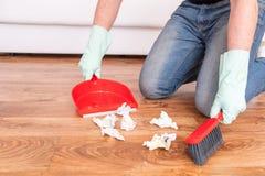 Σκουπίζοντας το ξύλινο πάτωμα με μικρό χτυπήστε ελαφρά τη σκούπα και dustpan στοκ φωτογραφία με δικαίωμα ελεύθερης χρήσης