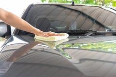 Σκουπίστε καθαρός το αυτοκίνητο με το ύφασμα και τη γυαλίζοντας κηρώνοντας κρέμα στοκ φωτογραφίες