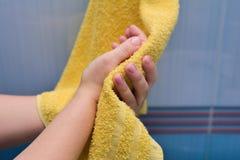 Σκουπίστε τα χέρια μια κίτρινη πετσέτα στοκ φωτογραφία με δικαίωμα ελεύθερης χρήσης