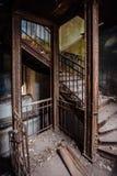 Σκουριασμένα εκλεκτής ποιότητας σκαλοπάτια σιδήρου με τα καρφιά στο παλαιό εγκαταλειμμένο μέγαρο Στοκ Φωτογραφία