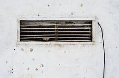 Σκουριασμένα παλαιά κάγκελα εξαερισμού στον τοίχο με ένα καλώδιο Στοκ φωτογραφίες με δικαίωμα ελεύθερης χρήσης