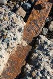 Σκουριασμένα σιδερόβεργα που γονιμοποιούνται μεταξύ των δύσκολων τσιμεντένιων ογκόλιθων Στοκ Φωτογραφίες